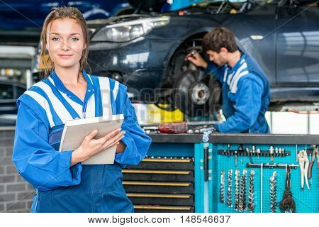Portrait of confident young female mechanic with maintenance checklist while colleague working in garage