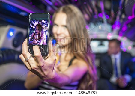 young, pretty, woman, holding a glass of champagne, taking a selfy with her cell phone inside a luxurious limousine