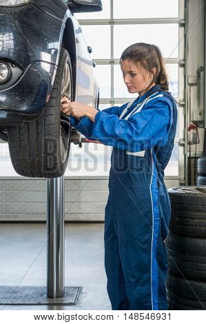 Young female mechanic in overalls changing car tire on lift at garage