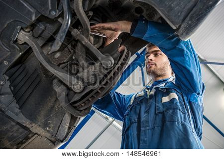Low angle view of male mechanic repairing suspension system of car in garage