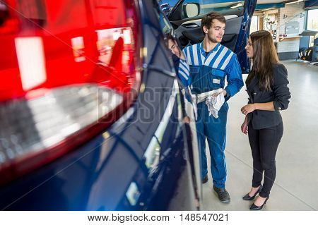 Young male mechanic discussing with businesswoman while standing by car at garage