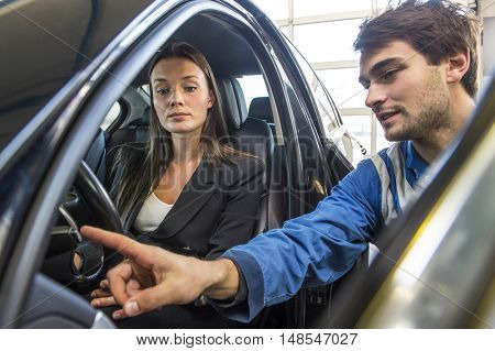 A mechanic in overalls explaining and instructing a customer, who has just bought a new car at a garage, as part of the after sales and service program
