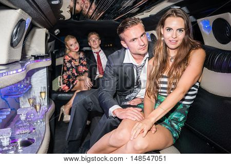 Elegant Young Couple With Friends In Limousine