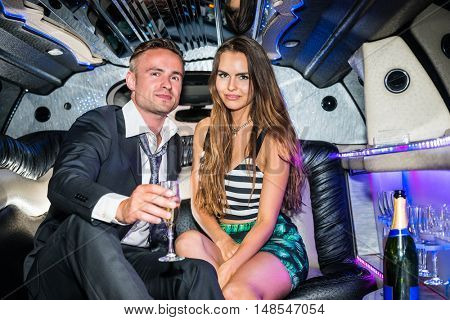 Young Glamorous Couple Sitting In Limousine