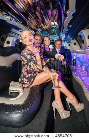 Beautiful Woman Blowing Kiss While Friends Partying In Limousine