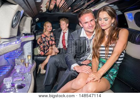 Elegant Couple With Friends Sitting In Luxurious Car