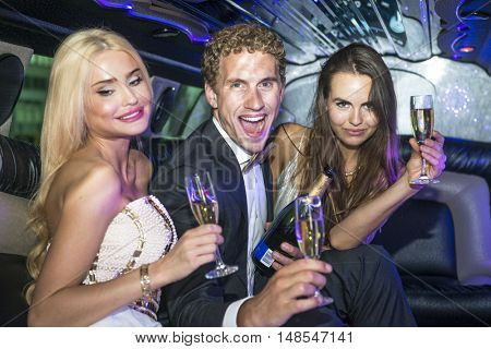 Rich and Famous young people drinking champagne and partying in a luxurious limousine