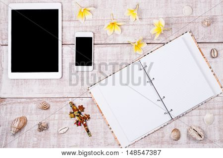 Tablet and smartphone lying on the wooden table with blank screen.