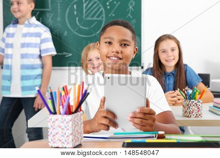 Pupil with tablet computer sitting in classroom