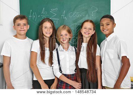 Schoolchildren standing in classroom near blackboard