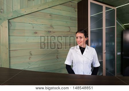 Woman on receptrion smiles and welcomes the virtual visitor at spa or modern clinic. Papers with agreement in your hand