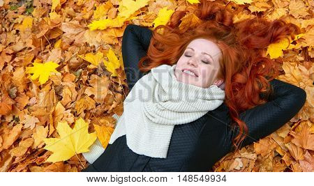girl lie on yellow fallen leaves in autumn forest background