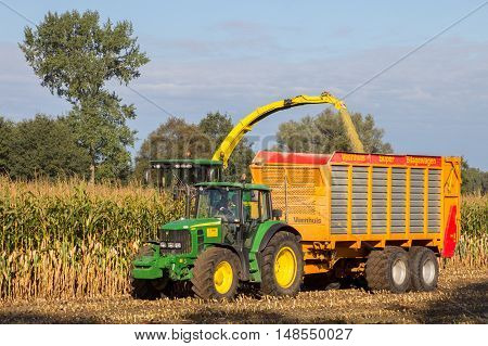 RUURLO THE NETHERLANDS - SEP 19 2016: John Deere 6930 tractor and John Deere 7480i Forage Harvester at work.