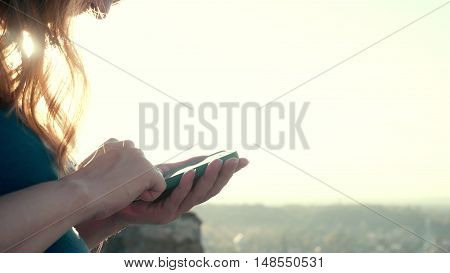 8 months pregnant young woman outdoor in nature at beautiful sunset. She use Phone