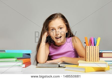Cute girl with books and stationery on grey background