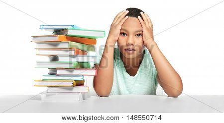 African American boy with books on light background