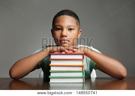African American boy with books on grey background