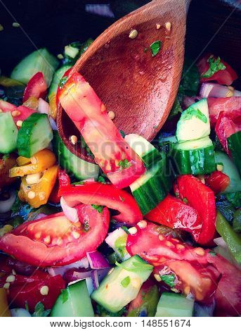Fresh chopped mixed salad and wooden spoon