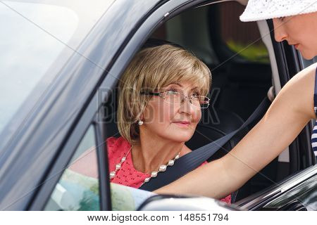 Portrait of attractive well-dressed senior woman asking about her location from passer