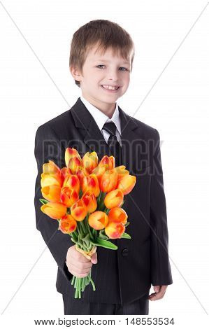 Portrait Of Cute Little Boy In Business Suit Giving Flowers To Somebody Isolated On White