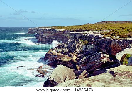 Weathered, rugged sandstone cliffs of Cape Solander, New South Wales coastline, Australia. Battered by wind and waves, rock collapse common.