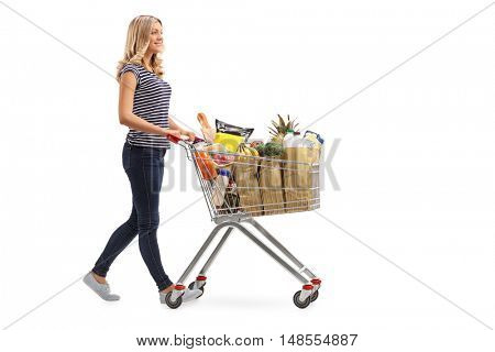 Full length portrait of a young woman pushing a shopping cart full of groceries isolated on white background