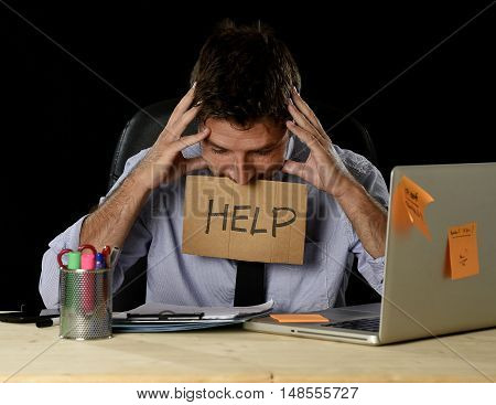 young desperate businessman suffering stress working at office computer desk holding sign asking for help looking tired exhausted and overwhelmed by heavy work load isolated on black background