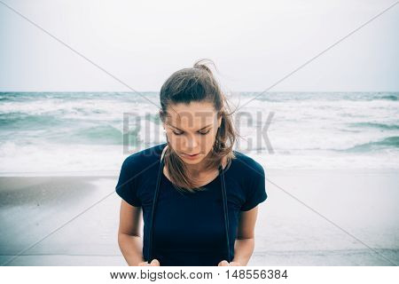 Attractive Female Athlete With A Skipping Rope On The Beach In Cold Weather