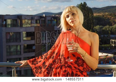 Beautiful woman standing on balcony in luxury hotel in Bulgaria at sunset and holding glass of wine.