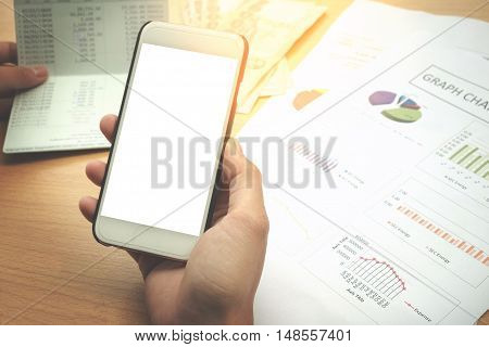 Hand holding using Mobile phone with blank screen on desk vintage style