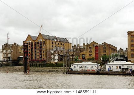 LONDON, ENGLAND - JULY 8, 2016: Wapping pier with the traditional riverside warehouses converted into high rise apartment and commercial blocks.