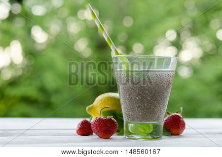 Chia seeds drink with water in transparent glass with lemon mint and strawberry. outdoor photo.