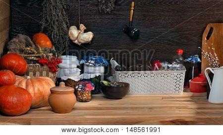 Domestic stocks with marinated vegetables in glass jars on a wooden shelf. Pantry. Pumpkins dishes boxes old things. Many items