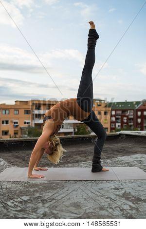 Woman practicing yoga on the roof,Ekopada Dhanurasana /Bridge pose with right leg up
