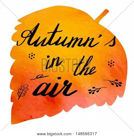 Hand written phrase Autumn's in the Air on abstract hand painted watercolor texture in leaf shape. Autumn foliage banner template with hand lettering isolated on white background. Vector illustration.