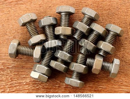 Many bolt and nut on wooden plate.