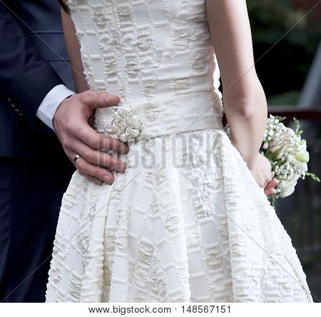 Couple on wedding day, man hugs woman, hands fragment, romantic photo of bride and groom on wedding day. Man and woman. Body part. Couple in love