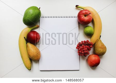 Notebook planner paper with blank empty page and colorful organic fresh fruits apple banana pear peach mango berries isolated on white table background Diet fitness planning, healthy eating food nutrition lifestyle concept with copy space close up