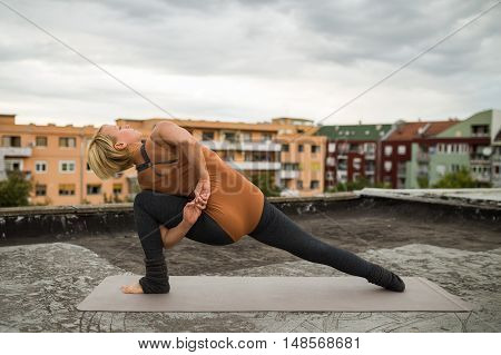 Woman is practicing yoga on the roof.