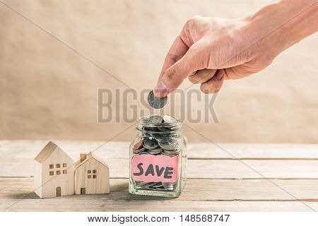 Male hand putting coin in glass jar of coin for saving money for buying house