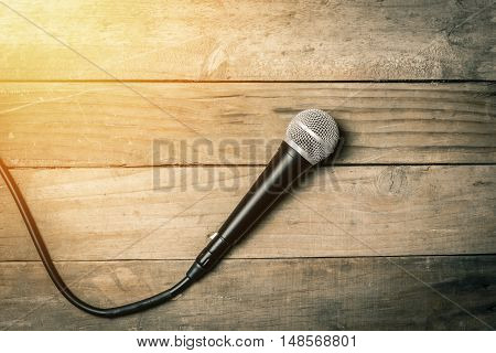 Microphone with cable on old vintage wooden background