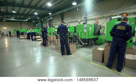 LUBLIN, POLAND - JUN 2016: Plastic Parts Workers Operate Equipment Manufacture.