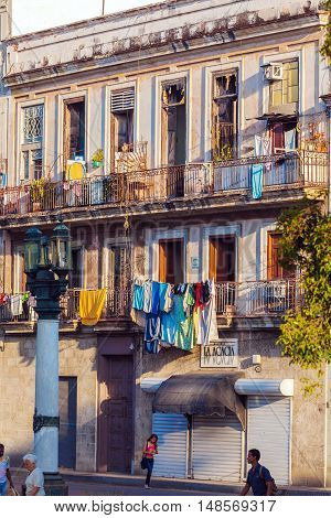 Havana, Cuba - April 2, 2012:  Tourists Walk Bear Vintage Houses Of Old City