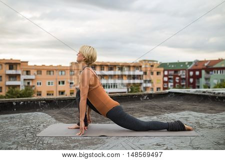 Woman practicing yoga on the roof,Anjaneyasana/Low lunge