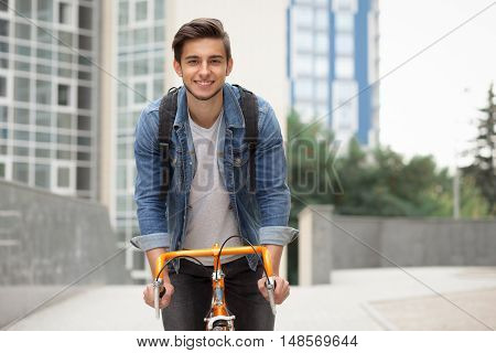 A guy in a blue denim jacket on orange bicycle. Man on the background of the city with a backpack on a bike