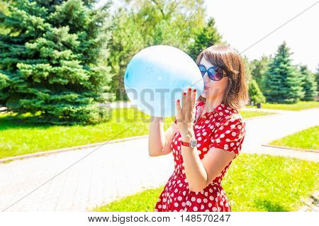 Portrait of the young beautiful smiling woman with balloons outdoor