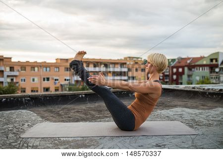Beautiful woman practicing yoga on the roof,Boat Pose/Navasana