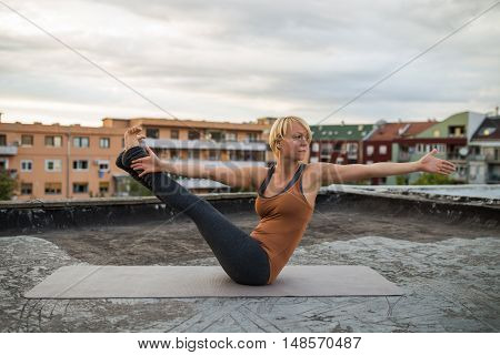 Woman is practicing yoga on the roof