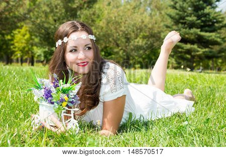 Portrait of the young beautiful smiling woman with long hair and flowers outdoors