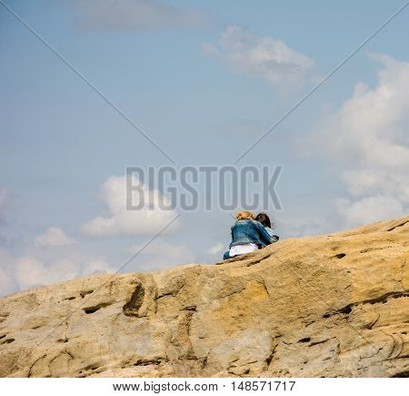 Mother and daughter sit on top of the mountain against the blue sky with white clouds